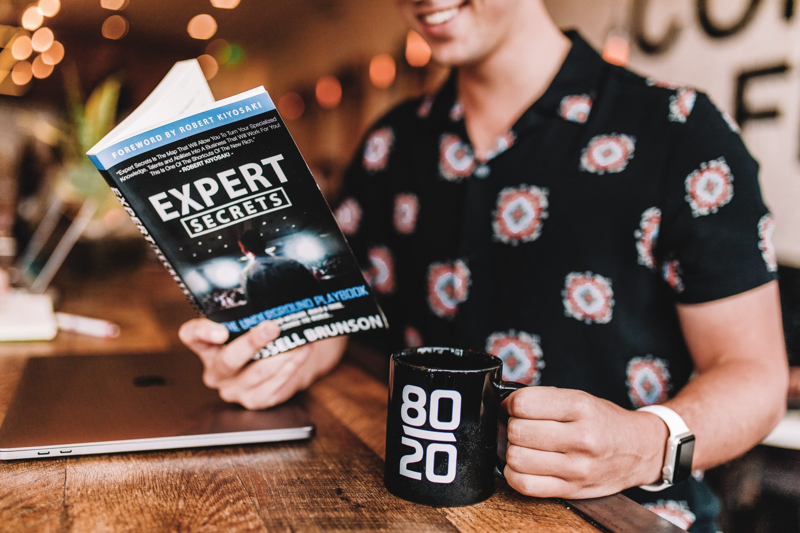 "A business owner looking to hire an expert reading a book about ""Expert Secrets"" while holding a coffee mug that says 80/20"