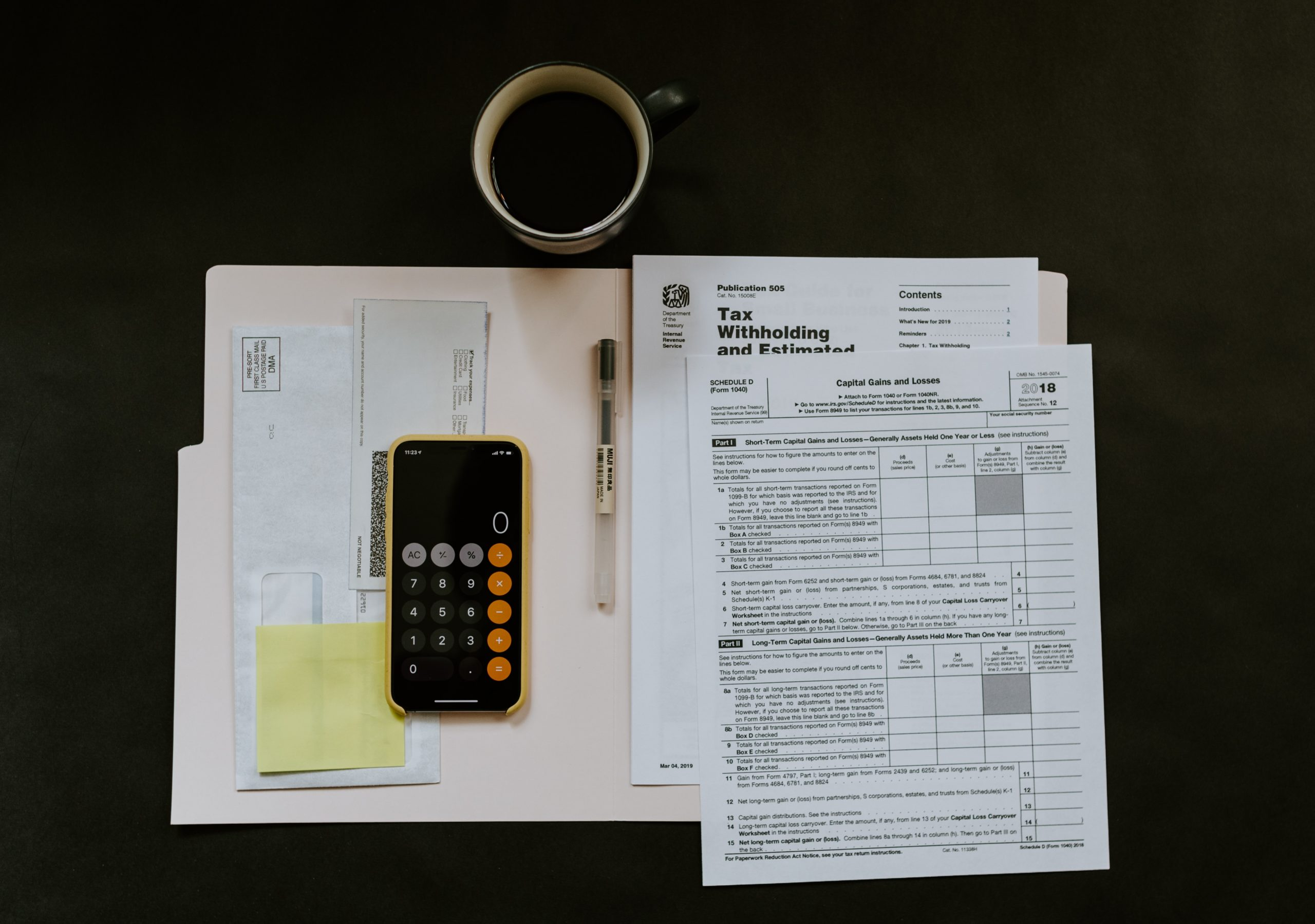 top view of various forms to be filled up for filing freelance taxes, includes a calculator and a cup of coffee
