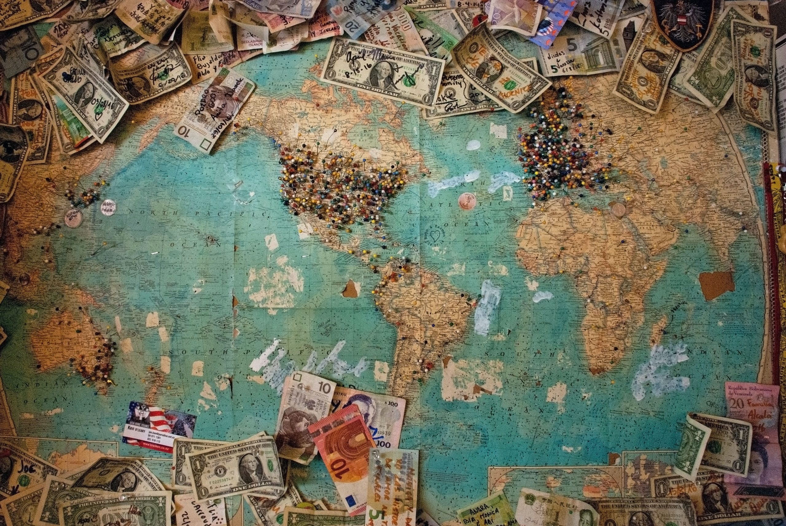 gain global advantage as described through a map of the world riddled with pins on the US and other countries and different monetary denominations scattered above and below the map