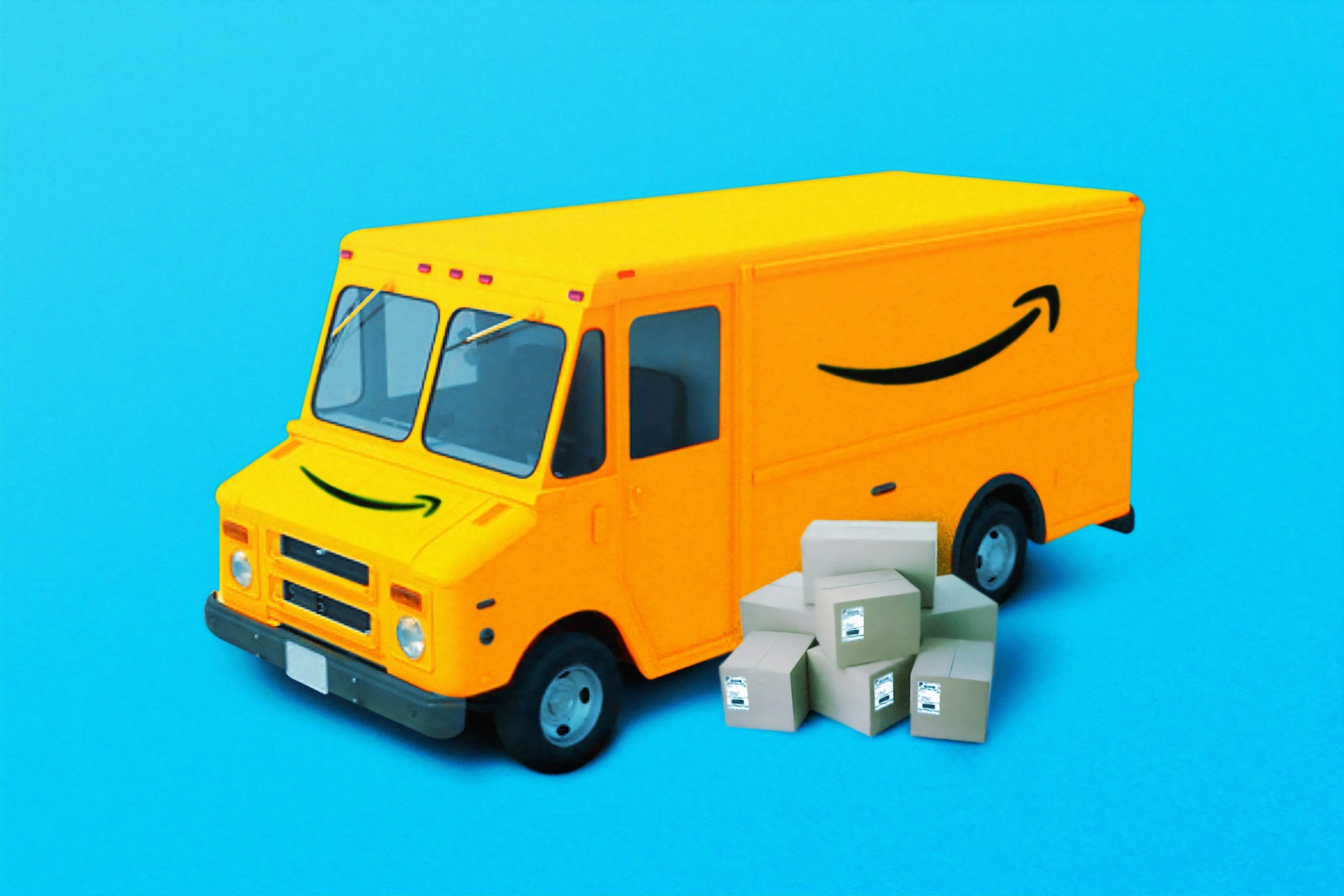 yellow amazon delivery truck with some boxes beside it