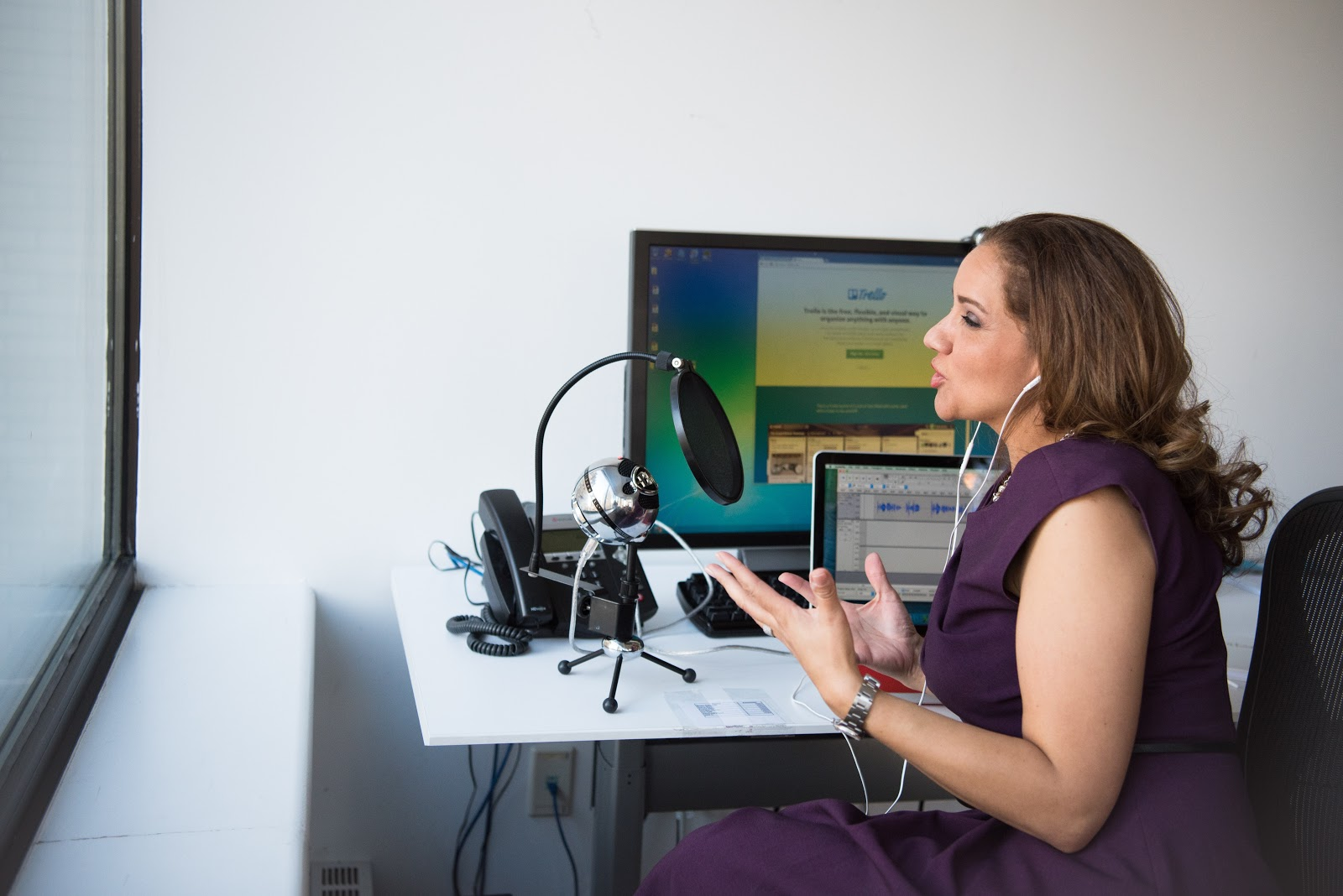 a woman recording her podcast using her desktop computer
