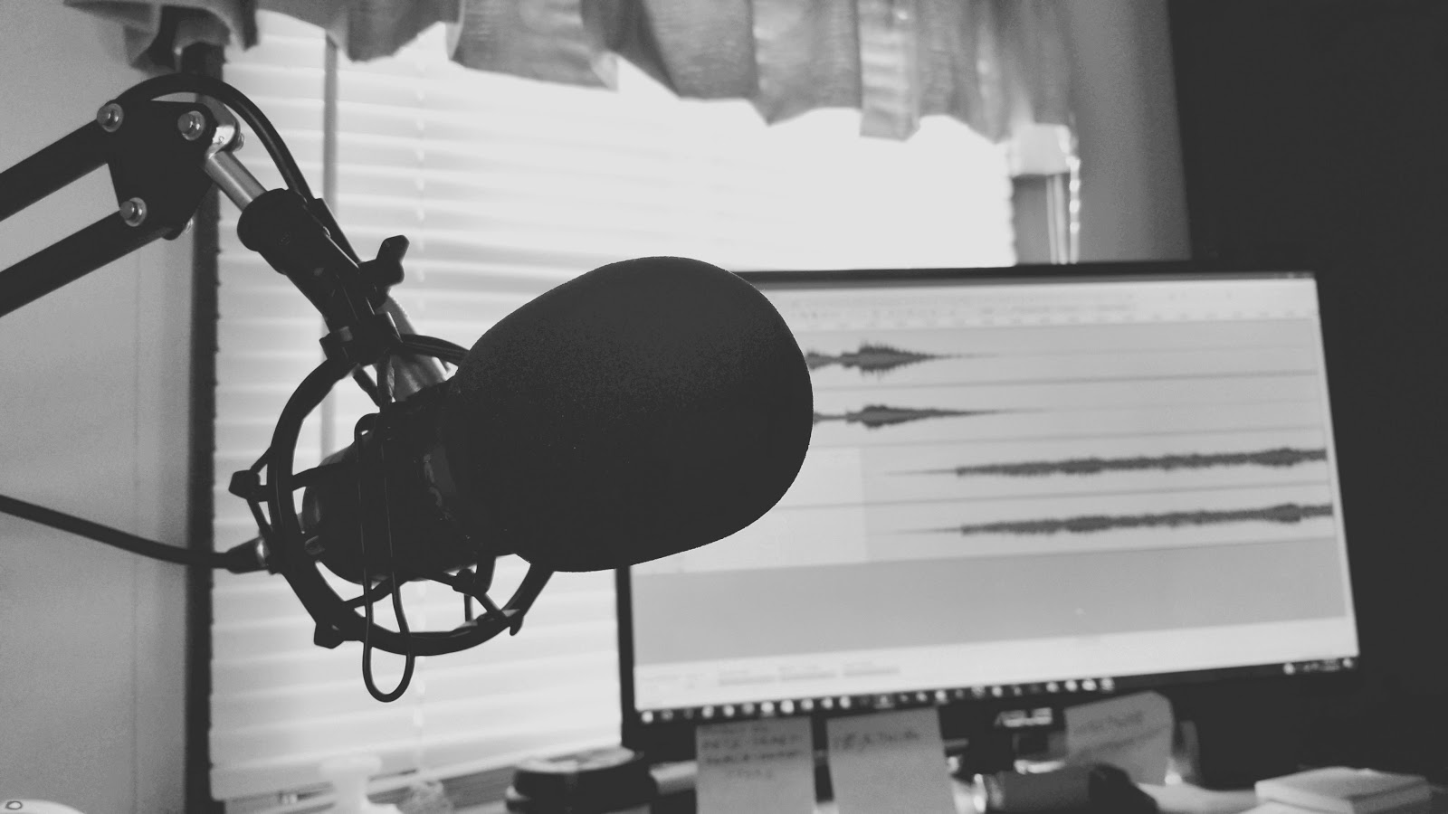 a mic in the left foreground and a monitor in the background that displays an audio recording