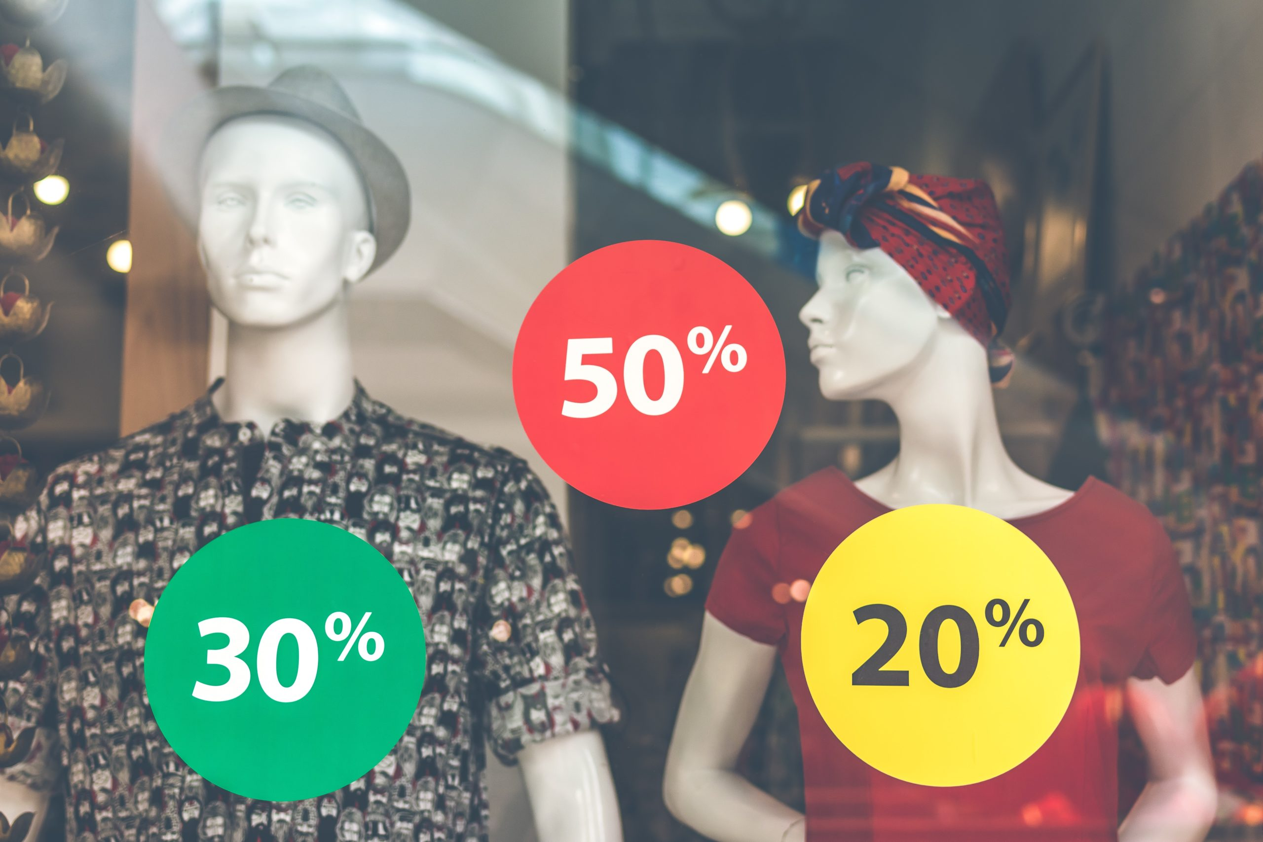 A shop's window display showing two mannequins with various percentage discounts to prices