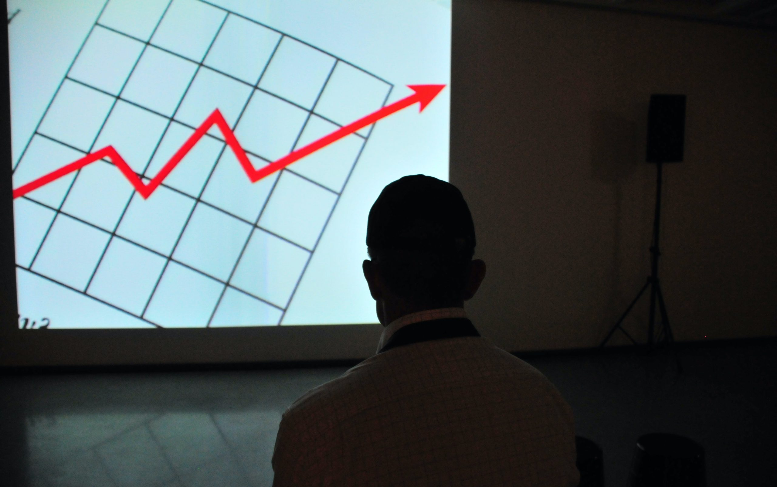 Man looking at power point presentation of a graph that shows an increasing trend in red