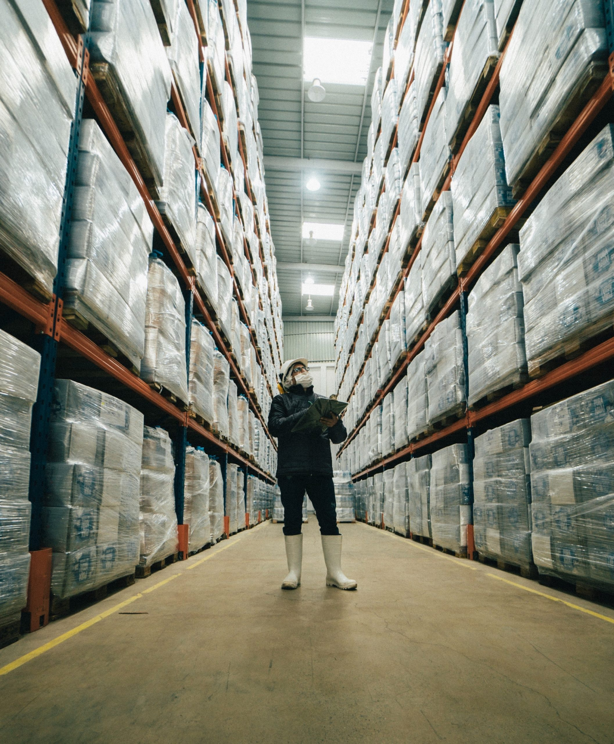A warehouse man managing an Amazon inventory while reconciling the number of the merchandize with that on his list