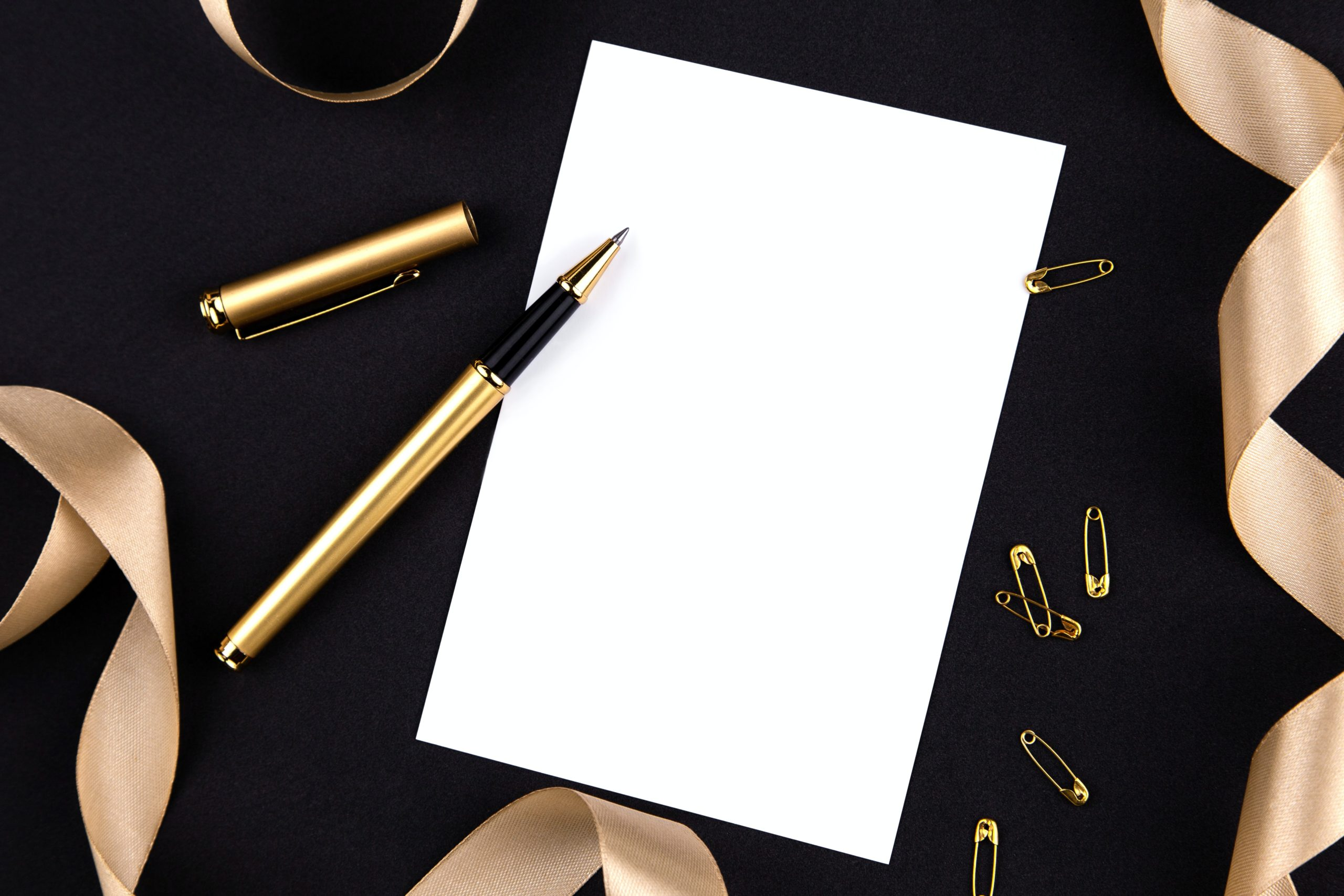 uncapped gold pen on a white piece of paper on a black background with some scattered gold safety pins and ribbons