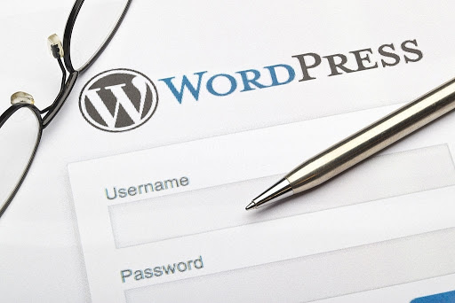 WordPress on paper together with glasses and a silver pen
