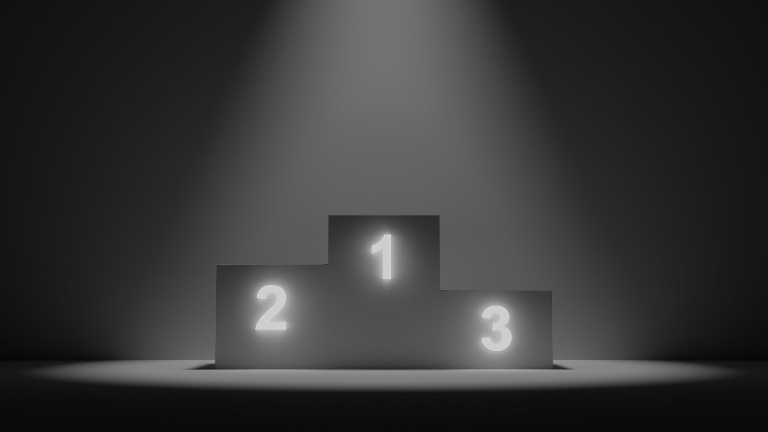 spotlight on a winner ranking stage with lighted numbers, one, two, and three.