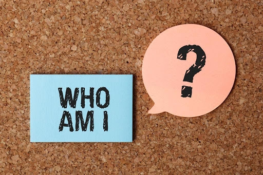 "written on a piece of paper are the words ""Who am I"" beside this is a question mark on another piece of paper shaped like a speech balloon"