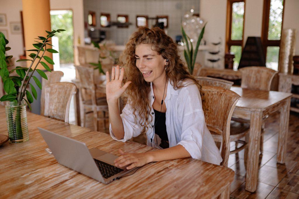woman waving in virtual meeting